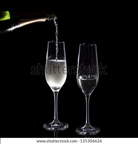 pouring champagne into two glasses - stock photo