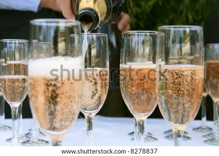Pouring Champagne into wine glasses - stock photo