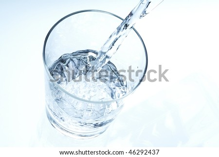 pouring clear water into a glass - stock photo