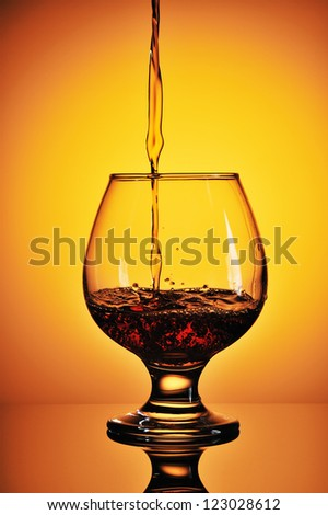 Pouring cognac in glass on a gold background - stock photo