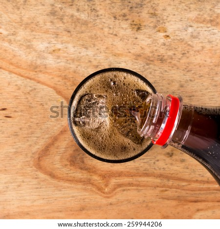 Pouring cola into the glass on wooden table,Top view. - stock photo