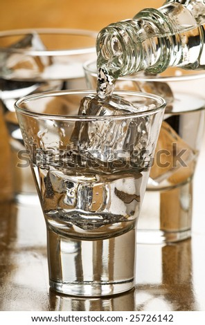 pouring cold vodka in to glass with ice cubes - stock photo