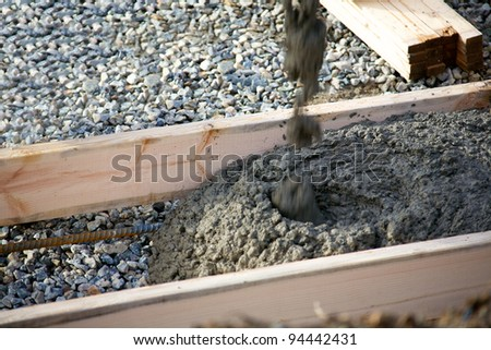 Pouring concrete for footings for a house under construction - stock photo