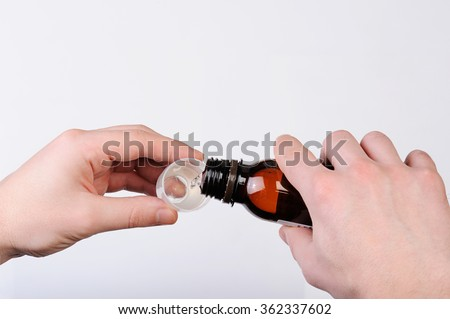pouring cough syrup from bottle to cup on white - stock photo