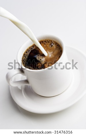 Pouring cream into a cup of coffee - stock photo