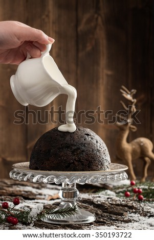 Pouring cream over Christmas pudding with festive setting - stock photo