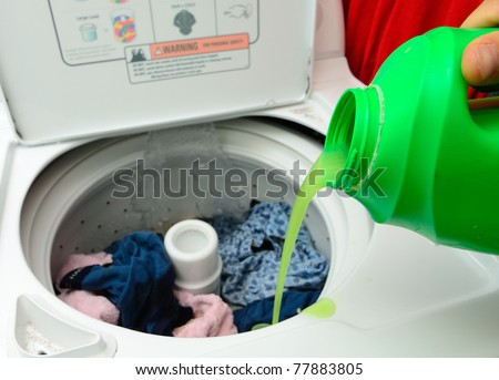 Pouring Detergent into the wash machine. - stock photo