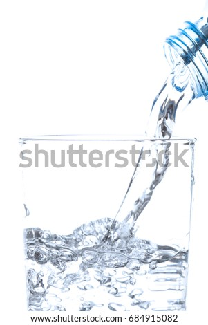 Pouring drinking water from bottle into glass on white background.