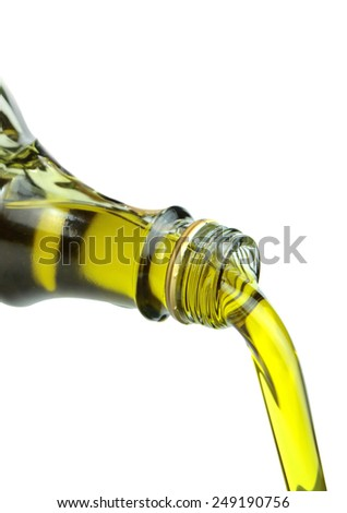 Pouring extra virgin olive oil from glass bottle on white background. Macro shot. - stock photo