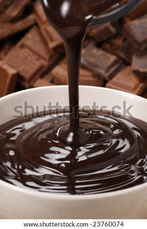 Pouring fresh chocolate cream on a white bowl. - stock photo