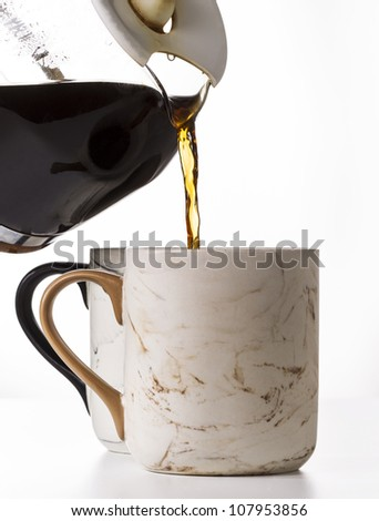 Pouring fresh coffee into porcelain mug on white background