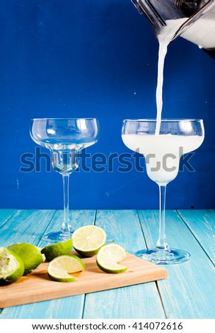 Pouring fresh frozen margarita from cup of blender with orange liquor in fancy margarita glass. Wood background with limes on wood plate - stock photo