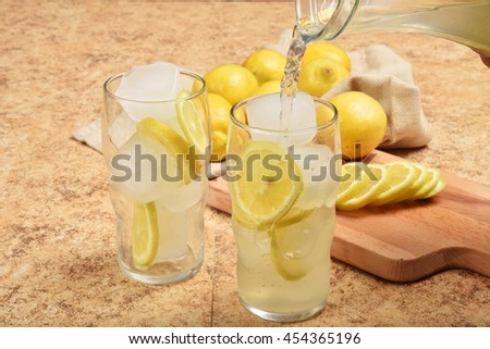 Pouring fresh squeezed lemonade into a glass - stock photo