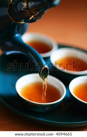Pouring fresh tea to elegant china teacups. - stock photo