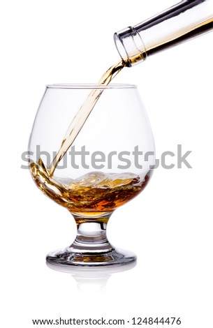 Pouring from bottle of cognac in glass isolated on white background - stock photo