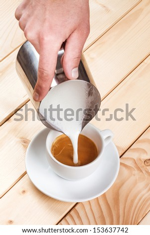 Pouring frothed milk into a cup of coffee, pattern creation - stock photo