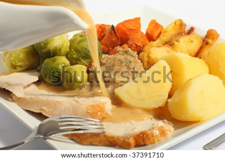 Pouring gravy on a festive turkey meal, with roast yams, roast parsnips, boiled potatoes and stuffing