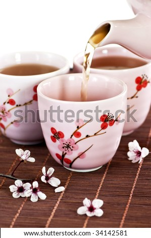 Pouring green tea into cups with cherry blossom design - stock photo