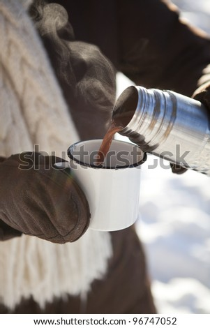 Pouring hot chocolate from a thermos to a mug on a winter day outdoors