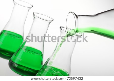 Pouring liquid chemicals into flask .