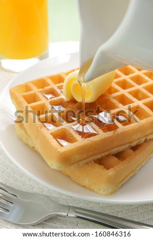 Pouring maple syrup on a stack of waffles - stock photo