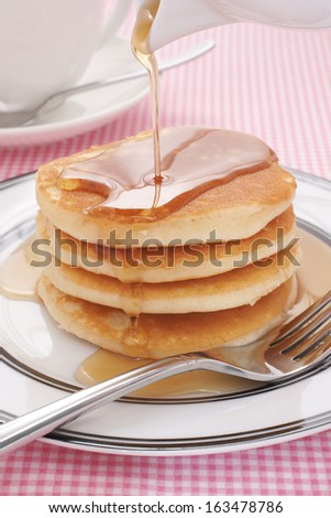 Pouring maple syrup on buttermilk pancakes - stock photo