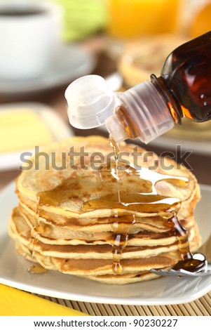 Pouring maple syrup on fresh homemade pancakes (Selective Focus, Focus on the front of the upper three pancakes) - stock photo