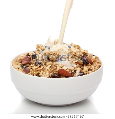 Pouring milk into a bowl with granola cereal - stock photo