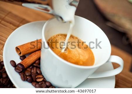 Pouring milk into coffee - stock photo