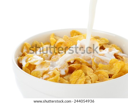 pouring milk into cornflakes bowl isolated on white - stock photo