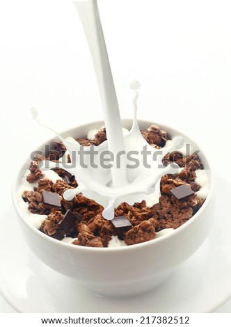 Pouring milk with a splash of droplets into a bowl of crunchy choc chip breakfast cereal rich in wheat, oats and bran for an energising low-CI start to the day - stock photo