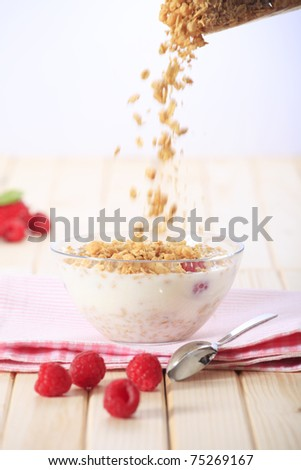 Pouring muesli on a bowl of milk with cereal (muesli/granola) and with fresh strawberries - stock photo