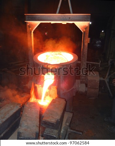 Pouring of liquid metal. Iron and steel industry. Foundry - molten metal poured from ladle   - stock photo