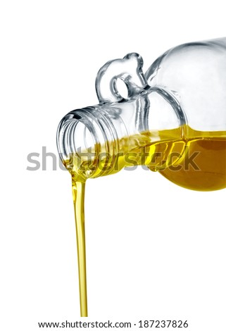 pouring olive oil from glass bottle against white background