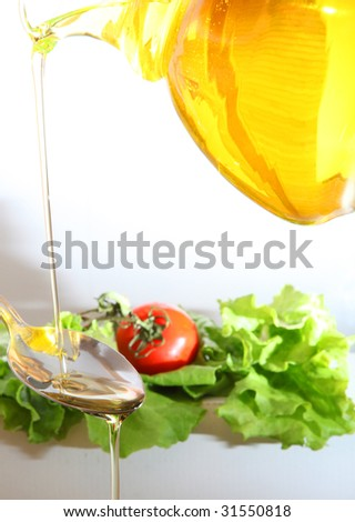 Pouring olive oil in the salad over a spoon - stock photo