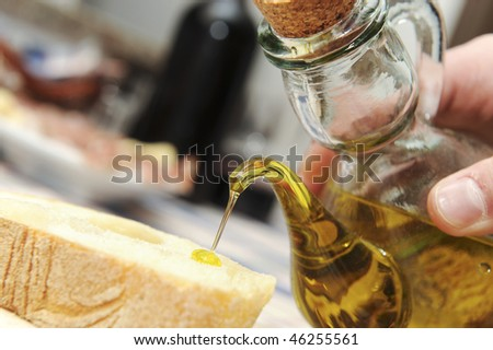 pouring olive oil on a bread slice - stock photo