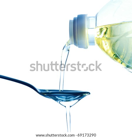 pouring olive oil on spoon, white background - stock photo