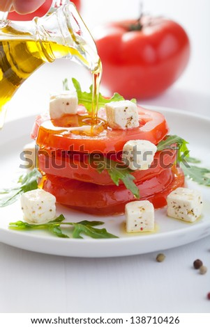 pouring olive oil over salad with beef tomatoes and feta - stock photo
