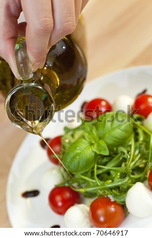 Pouring olive oil salad dressing onto tomato, mozzarella and rocket salad with basil garnish and balsamic vinegar - stock photo