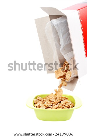Pouring out cereals in a bowl isolated on white background. Shallow depth of field - stock photo