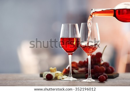 Pouring pink wine from bottle into the wineglass on blurred background - stock photo