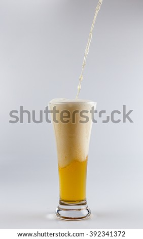 Pouring process of lager beer into a beer glass, splashes, drops and froth around glass against white background - stock photo