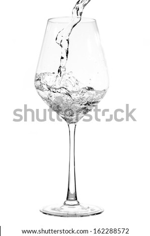 Pouring pure water into a glass isolated on white background - stock photo