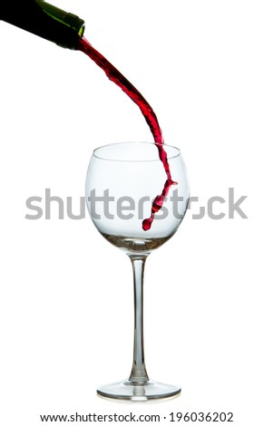 pouring red wine from bottle into glass - stock photo