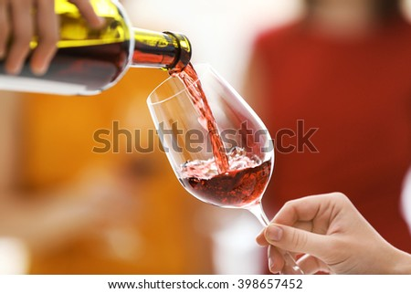 Pouring red wine from bottle into glass, close up - stock photo