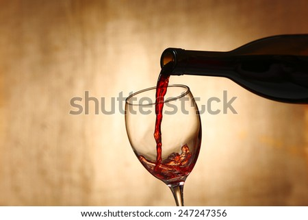 Pouring red wine from bottle into glass on blurred background - stock photo
