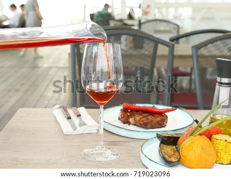 Pouring red wine from decanter into glass on served table