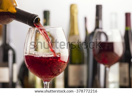 pouring red wine in glass with bottles on background - stock photo