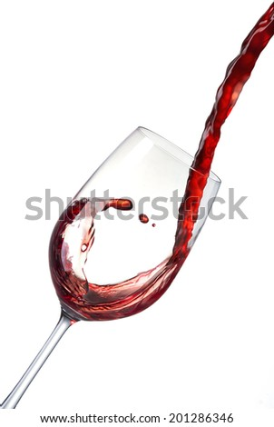 Pouring red wine into a crystal glass and creates waves, splash. Red wine poured from bottle into a glass isolated on white background  - stock photo