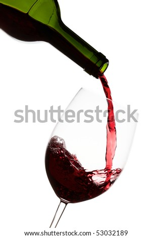 Pouring red wine into a crystal wine glass over white background - stock photo